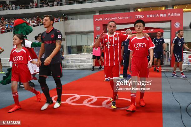 Franck Ribery of Bayern Muenchenjokes with the escort kid as he walk in for the Audi Football Summit 2017 match between Bayern Muenchen and Arsenal...