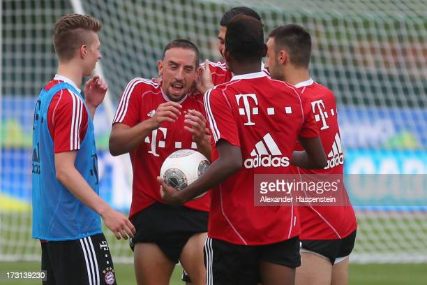 Franck Ribery of FC Bayern Muenchen jokes with his team mates Mitchel Weiser Emre Can David Alaba and Diego Contento after a training session at...