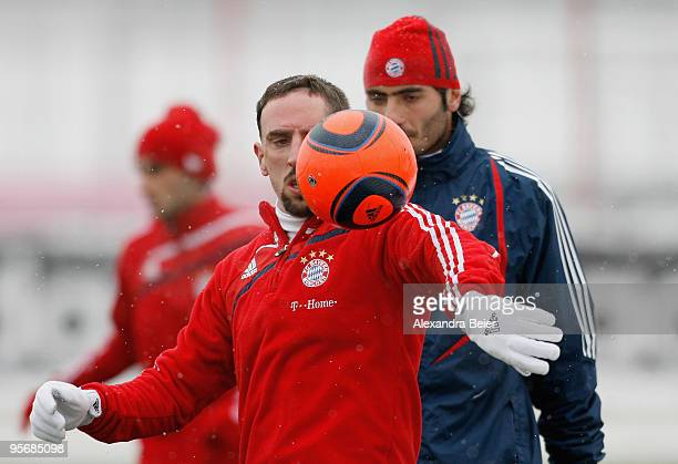 Franck Ribery of FC Bayern Muenchen plays with a ball in front of Hamit Altintop during the team's first training session after a training camp in...