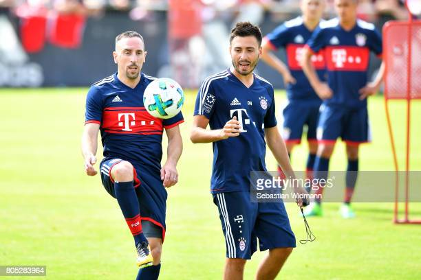 Franck Ribery of FC Bayern Muenchen plays with a ball while assistant coach Davide Ancelotti watches him during a training session at Saebener...