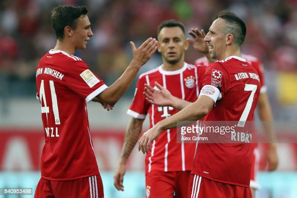 Franck Ribery of Muenchen celebrates his team's fourth goal with team mates Alexander Nitzel and Rafinha during a friendly match between Kickers...