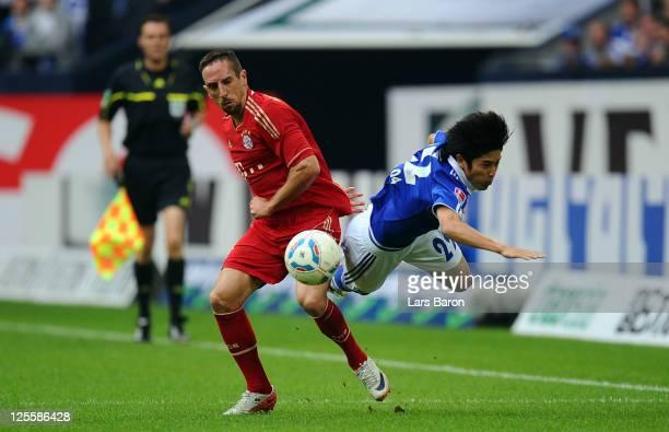 Franck Ribery of Muenchen challenges Atsuto Uchida of Schalke during the Bundesliga match between FC Schalke 04 and FC Bayern Muenchen at Veltins...