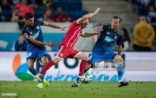 Franck Ribery of Muenchen is challenged by Nadiem Amiri and Eugen Polanski of Hoffenheim during the Bundesliga match between TSG 1899 Hoffenheim and...