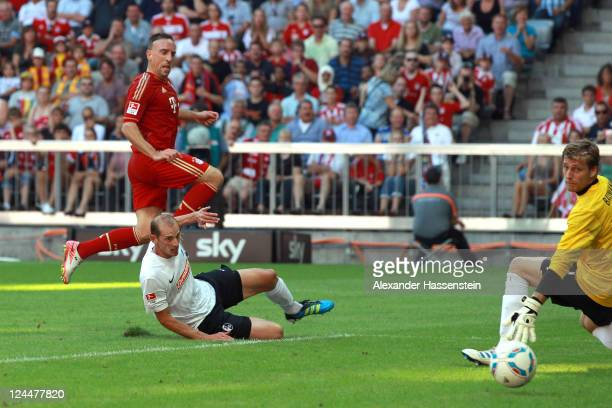 Franck Ribery of Muenchen scores the third team goal against Oliver Barth of Freiburg and his keeper Oliver Baumann during the Bundesliga match...