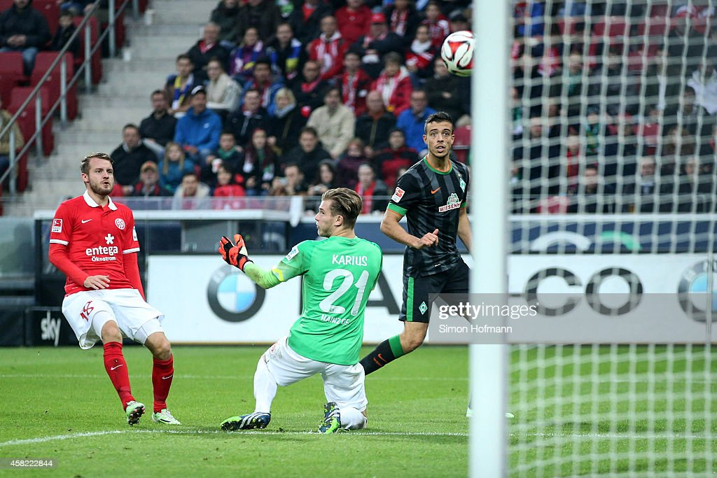 Franco di Santo of Bremen scores his team's second goal against goalkeeper Loris Karius and <a gi-track='captionPersonalityLinkClicked' href=/galleries/search?phrase=Daniel+Brosinski&family=editorial&specificpeople=654244 ng-click='$event.stopPropagation()'>Daniel Brosinski</a> of Mainz during the Bundesliga match between 1. FSV Mainz 05 and SV Werder Bremen at Coface Arena on November 1, 2014 in Mainz, Germany.
