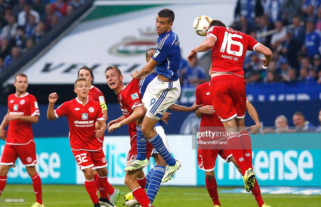 Franco di Santo of Schalke (C) jumps for a header against Jhon Cordoba of Mainz (R) during the Bundesliga match between FC Schalke 04 and 1. FSV Mainz 05 at Veltins-Arena on September 13, 2015 in Gelsenkirchen, Germany.