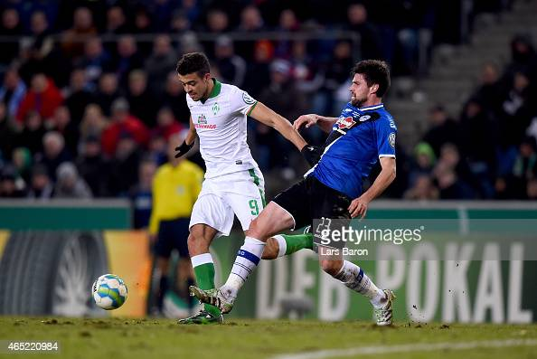 Franco Di Santo of Werder Bremen is challenged by Florian Dick of Arminia Bielefeld during the round of 16 DFB Cup match between Arminia Bielefeld...