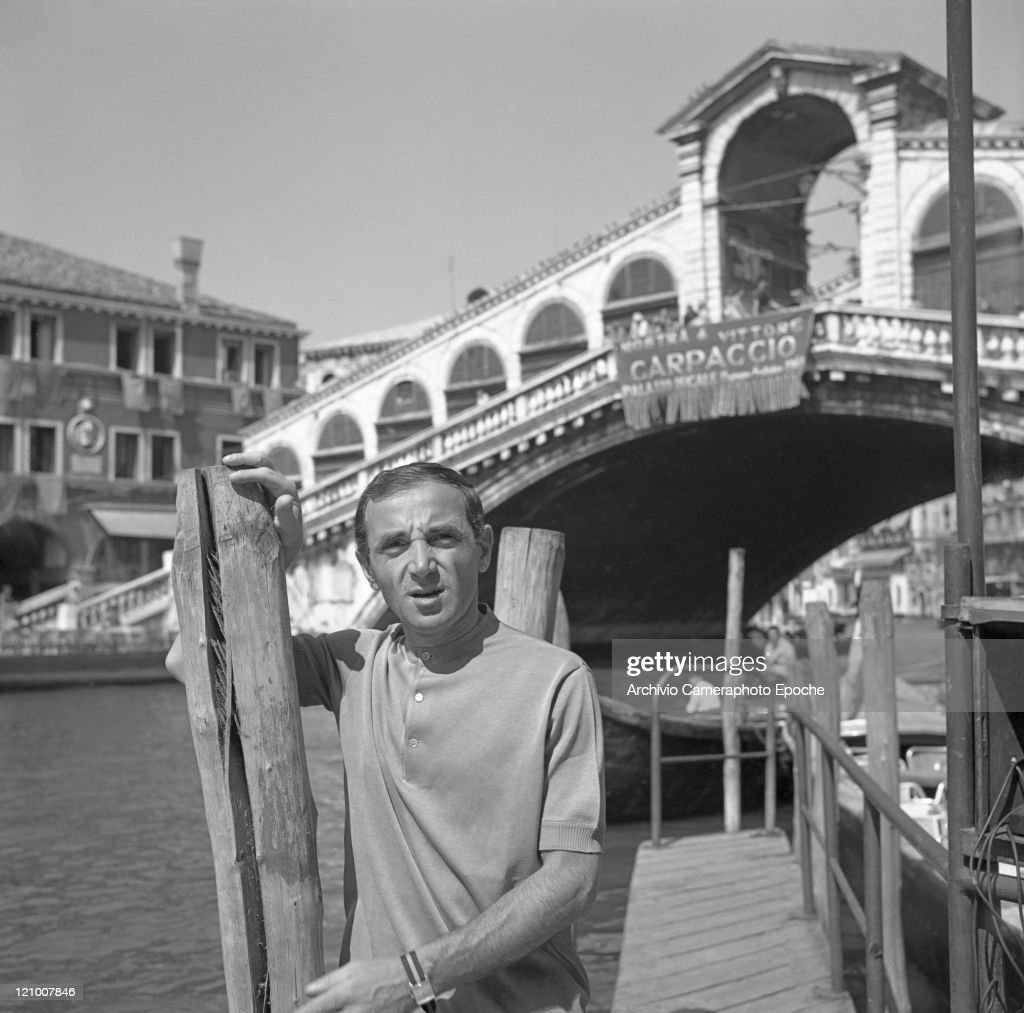 Francoarmenian singer Charles Aznavour portrayed in front of Rialto bridge leaning on a wooden pole Venice 1970s