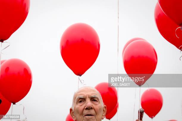 FrancoGerman former diplomat Stephane Hessel is surrounded by red balloons as he attends on November 24 2011 on the famous Ponts des Arts a tribute...