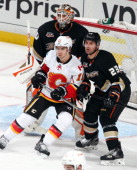 Francois Beauchemin and Viktor Fasth of the Anaheim Ducks defend the net against Mikael Backlund of the Calgary Flames on October 16 2013 at Honda...