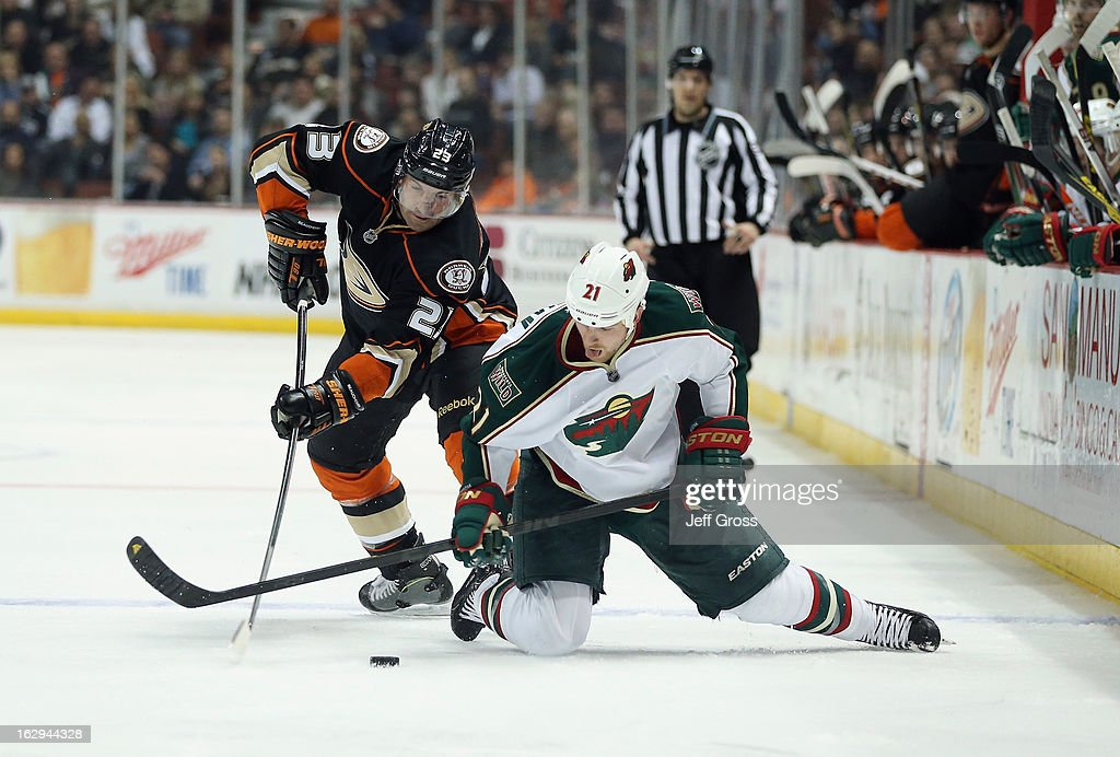 Francois Beauchemin #23 of the Anaheim Ducks and Kyle Brodziak #21 of the Minnesota Wild fight for the puck in the second period at Honda Center on March 1, 2013 in Anaheim, California.