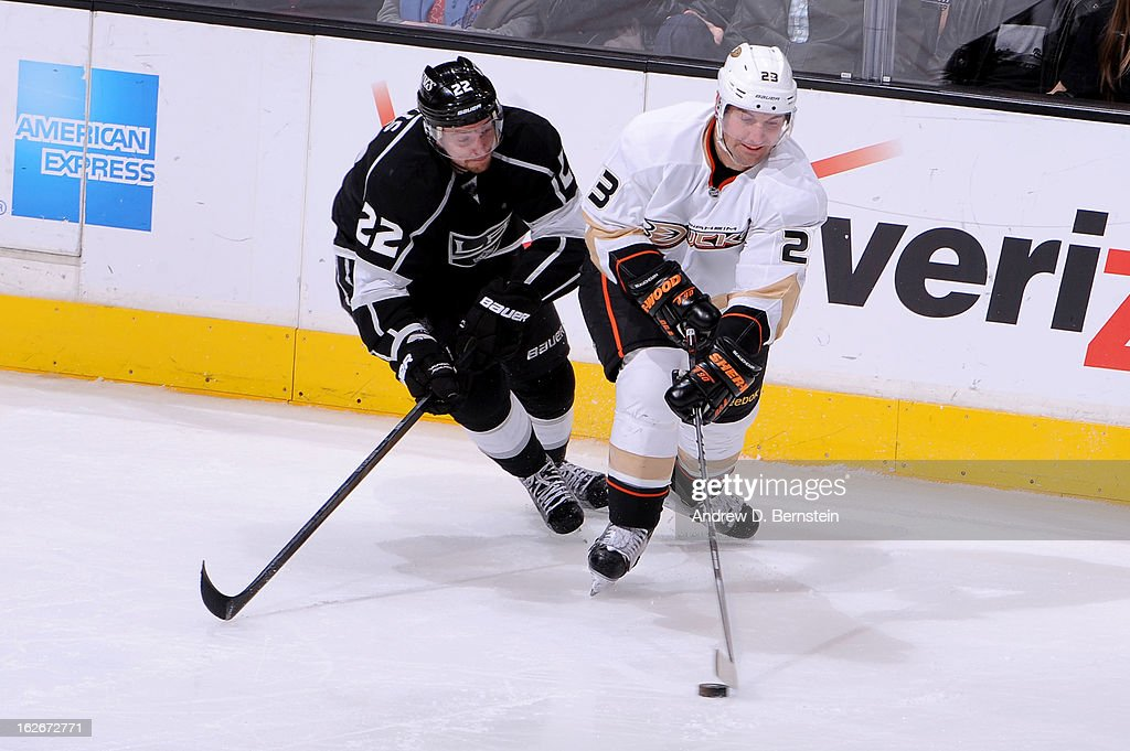 Francois Beauchemin #23 of the Anaheim Ducks skates with the puck against Trevor Lewis #22 of the Los Angeles Kings at Staples Center on February 25, 2013 in Los Angeles, California.