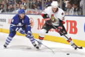 Francois Beauchemin of the Toronto Maple Leafs battles for the puck with Alexei Kovalev of the Ottawa Senators during game action October 6 2009 at...