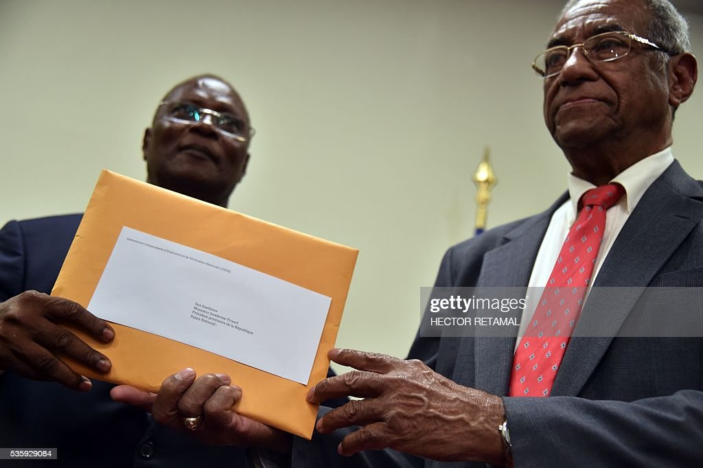 Francois Benoit (R), president of the special election commission, delivers the commission's investigative report on the 2015 Haitian election to Haitian Provisional President Jocelerme Privert (L) at the National Palace in Port-au-Prince, on May 30, 2016. The commission proposes rerunning the presidential election of 2015. / AFP / HECTOR