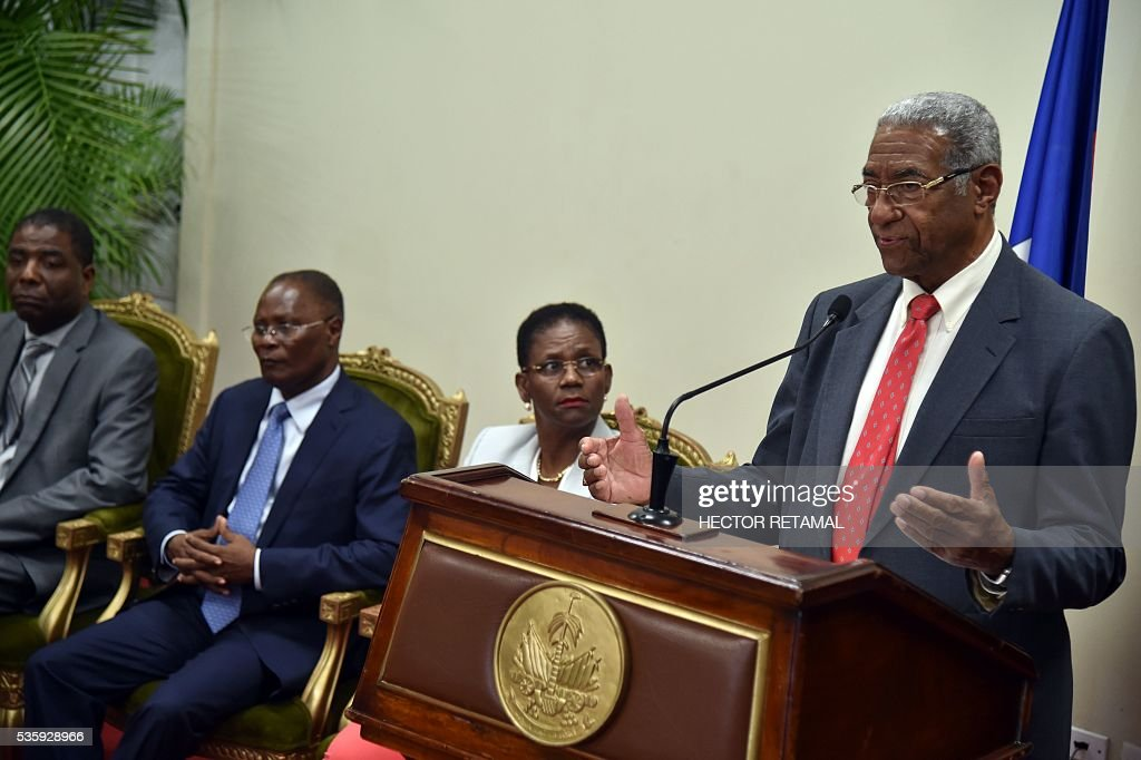 Francois Benoit (R), president of the special election commission, speaks after delivering the commission's investigative report on Haiti's 2015 election at the National Palace in Port-au-Prince, on May 30, 2016. The commission proposes rerunning the presidential election of 2015. / AFP / HECTOR
