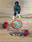 Francois Etoundi of Australia celebrates a successful lift on his way to a bronze medal in the Men's Weightlifting 77kg category at Scottish...