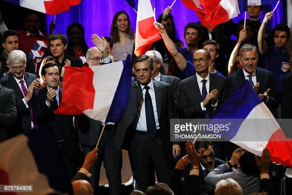 Francois Fillon candidate for the rightwing primaries ahead of the French 2017 presidential election waves flanked by Eric Woerth French member of...