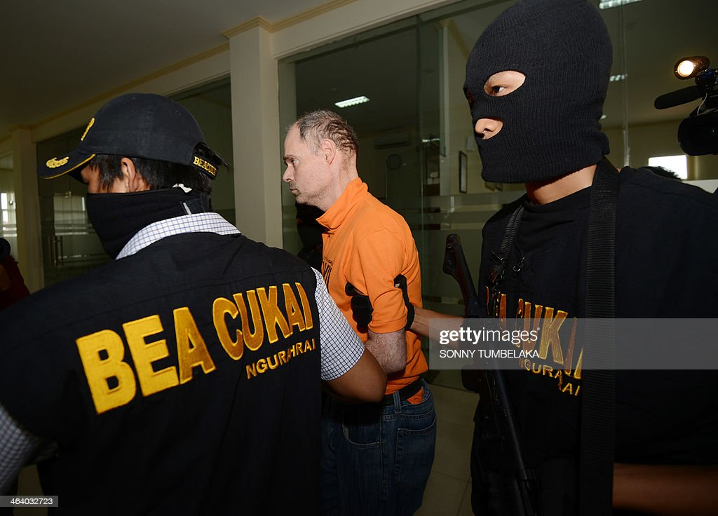 Francois Jacques Giuily of France is escorted by customs security inside the Custom office in Denpasar on January 20, 2014. Giuily was arrested on January 19 carrying 3.083 grams of methamphetamine in his luggage at Bali International Airport in Indonesia, officials said. AFP PHOTO / SONNY TUMBELAKA