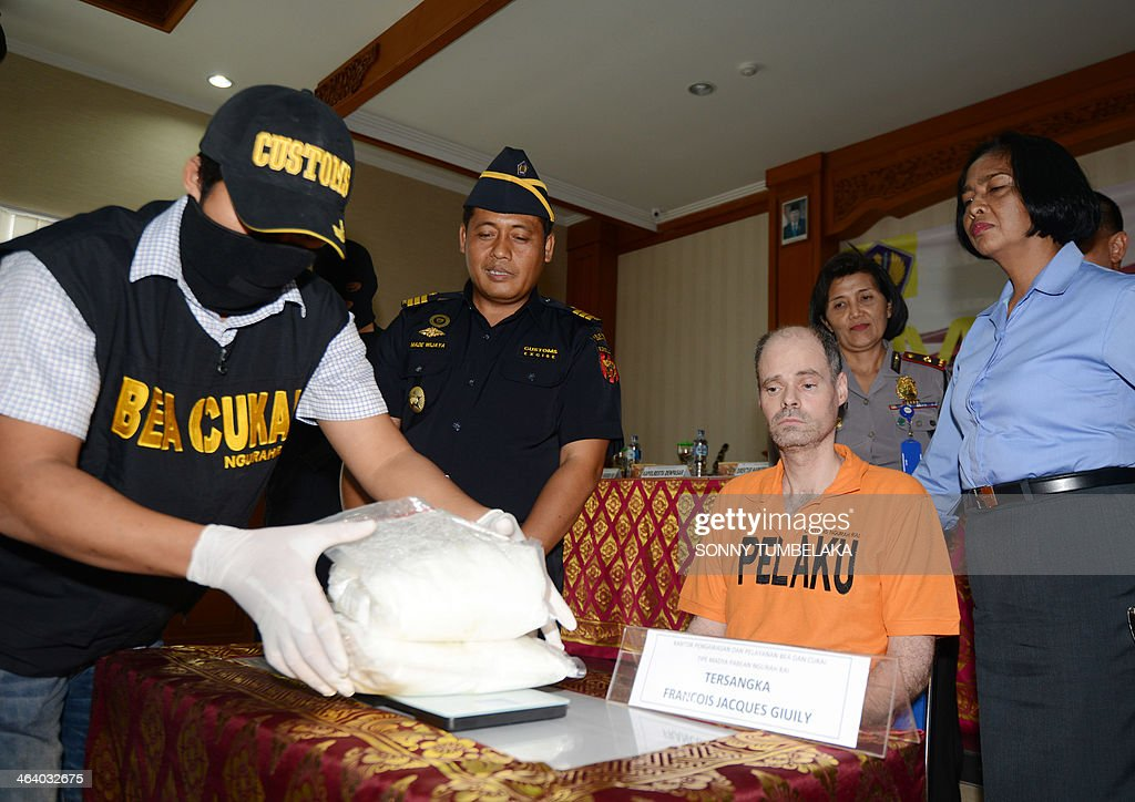 Francois Jacques Giuily (2nd R) of France sits near evidence of methamphetamine at the Custom office in Denpasar on January 20, 2014. Giuily was arrested on January 19 carrying 3.083 grams of methamphetamine in his luggage at Bali International Airport in Indonesia, officials said.