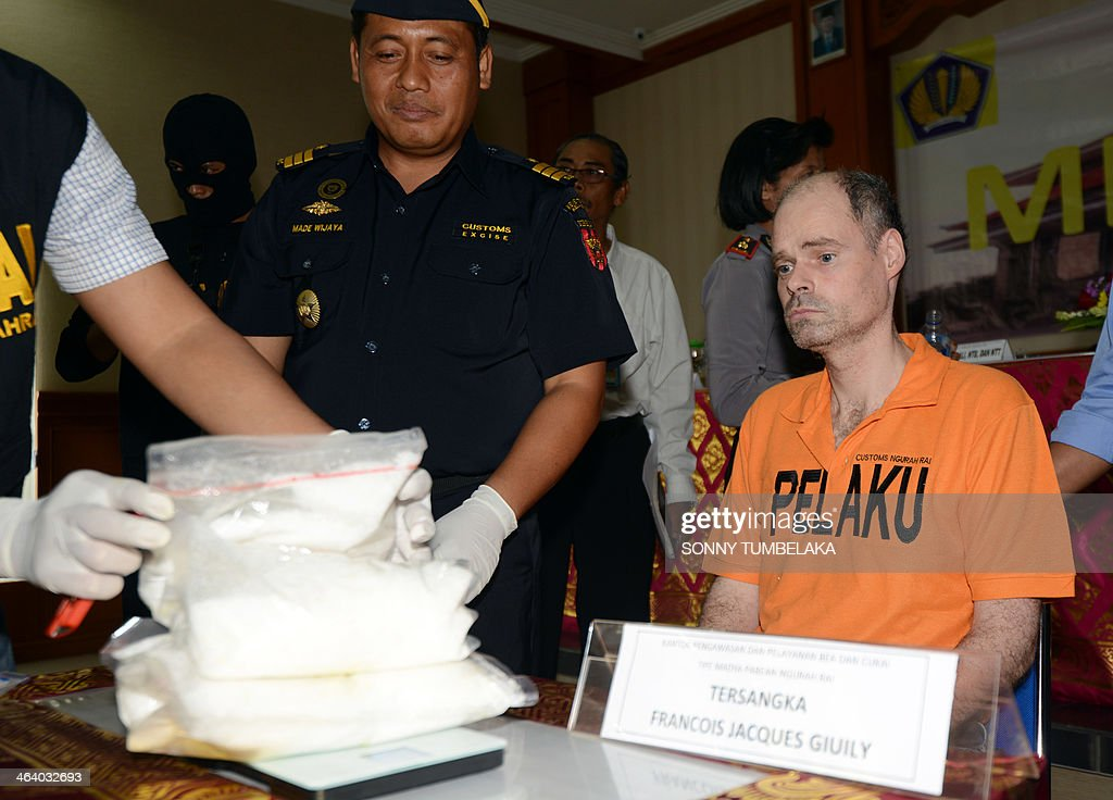 Francois Jacques Giuily (R) of France sits near evidence of methamphetamine at the Custom office in Denpasar on January 20, 2014. Giuily was arrested on January 19 carrying 3.083 grams of methamphetamine in his luggage at Bali International Airport in Indonesia, officials said.