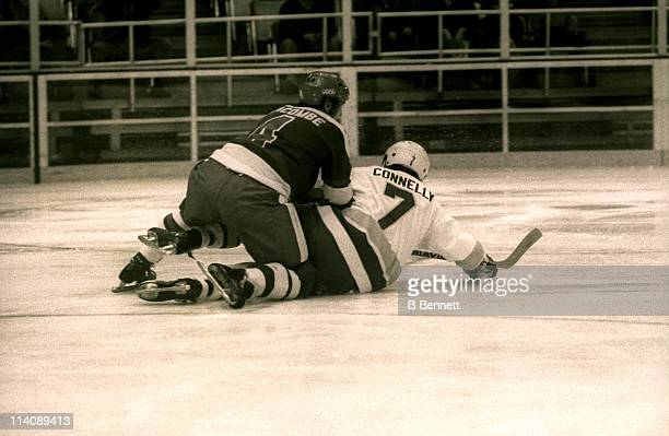 Francois Lacombe of the Quebec Nordiques checks Wayne Connelly of the Minnesota Fighting Saints during their game on April 2 1975 at the St Paul...