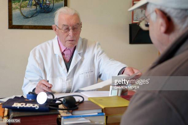 MEYER Francois Le Men a 91 yearold doctor fills a prescription for a patient at the end of a consultation on June 11 2013 in Callac western France...