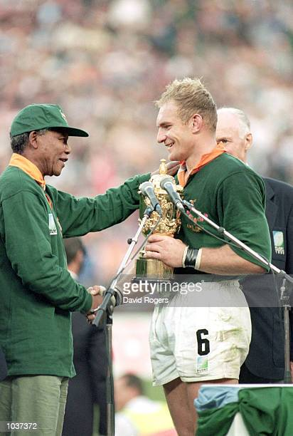 Francois Pienaar of South Africa receives the William Webb Ellis Trophy from President Nelson Mandela after the Rugby World Cup final between South...
