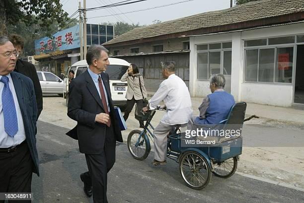 Francois Roussely Edf Ceo In Beijing China Francois ROUSSELY président d'EDF regardant passer un couple âgé dans un triporteur alors qu'il se rend à...