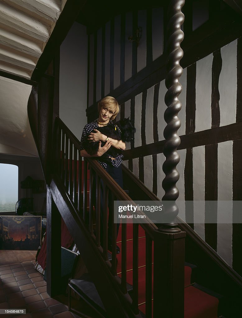 Francoise Sagan posing with her dog in her arms on the stairs of his house in Normandy