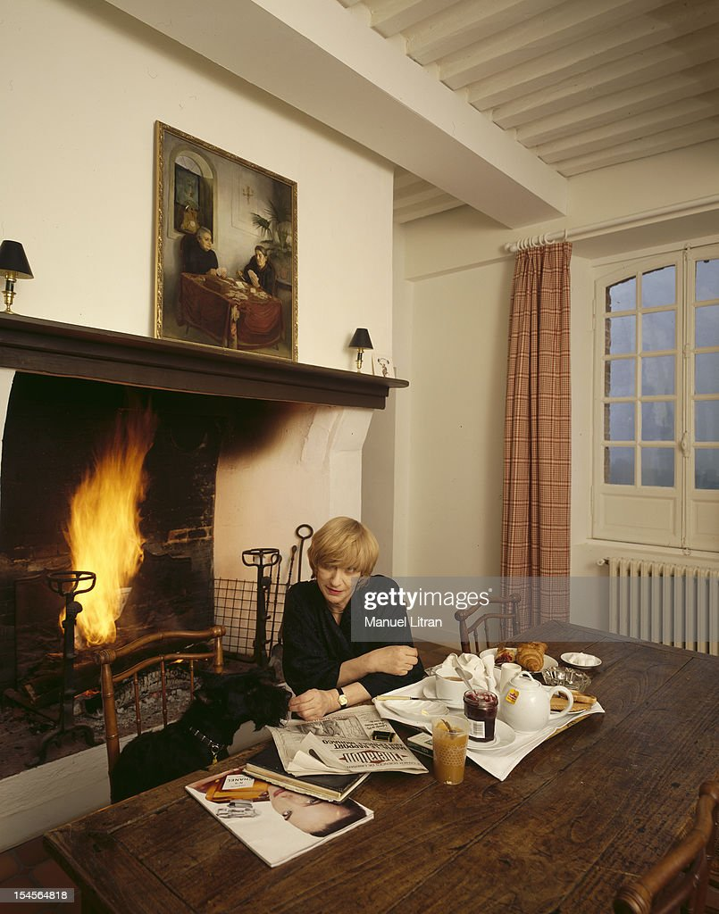 Francoise Sagan reading newspapers sitting at a table with her dog in front of a chimney fire in her house in Normandy