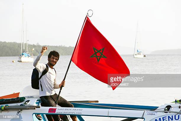 FrancoMoroccan Said Ben Amar holds a Morrocan flag as he celebrates on March 21 2012 off the coasts of the city of Cayenne after crossing the finish...