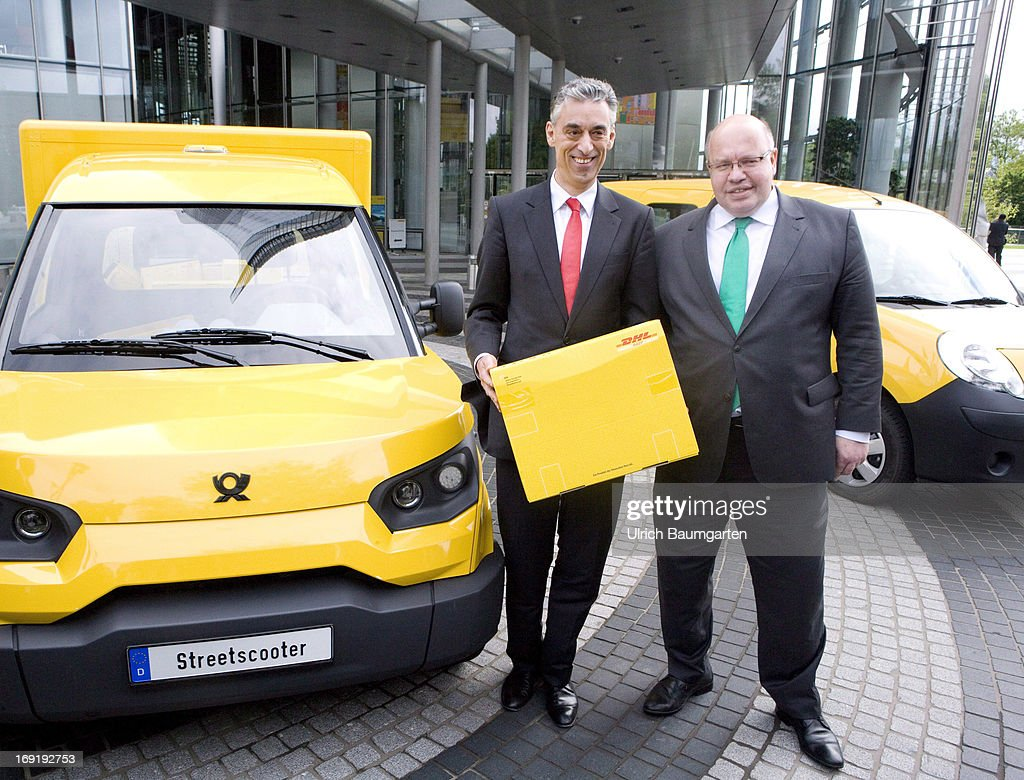 Frank Appel (L), CEO of the Deutsche Post DHL, and Federal Minister of Environment Peter Altmaier (CDU) stand beside a carbon-neutral mail delivery vehicle on May 21, 2013 in Bonn, Germany. Initially 79 vehicles will be put into service in Bonn and the surrounding area for delivery.