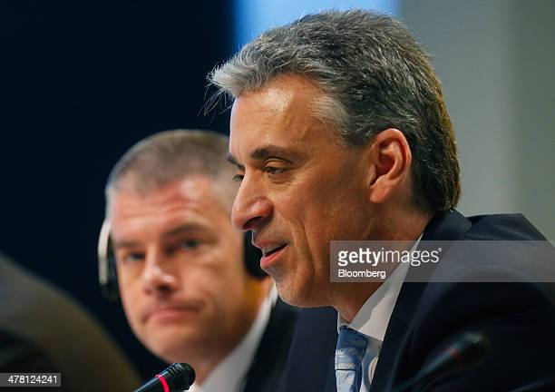 Frank Appel chief executive officer of Deutsche Post AG right speaks during a news conference while John Gilbert member of the board of Deutsche Post...