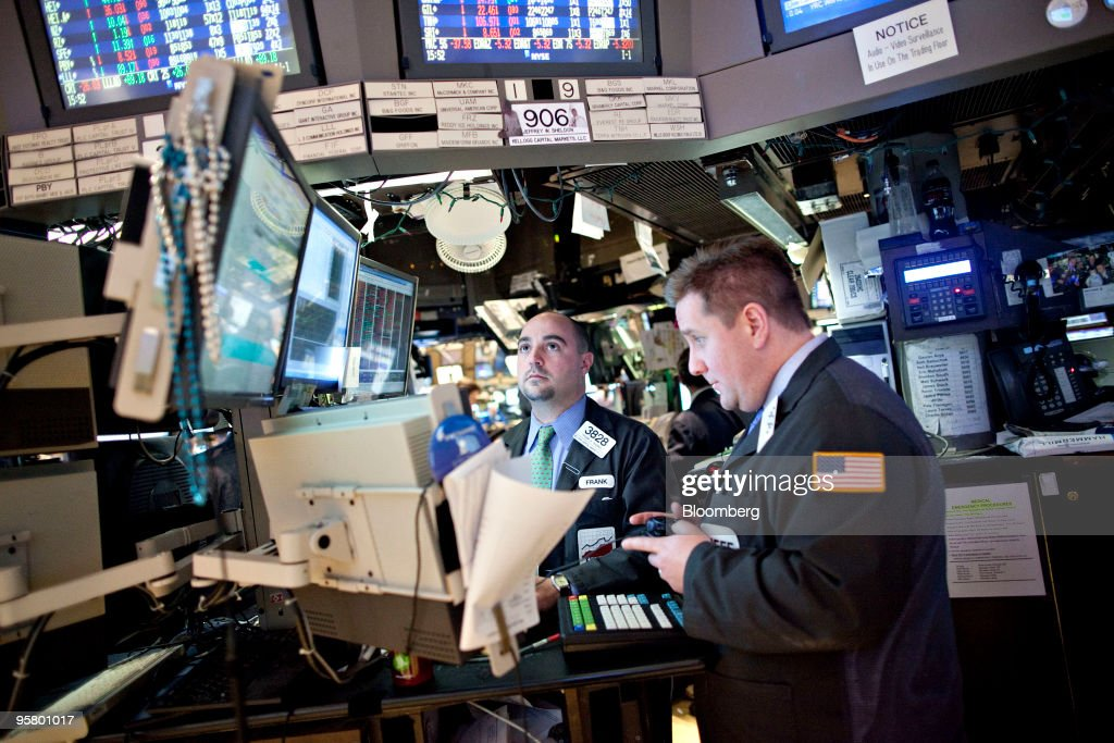 Frank Babino center and Jeffrey Sheldo work at a post on the floor of the New York Stock Exchange in New York US on Friday Jan 15 2010 US stocks and...