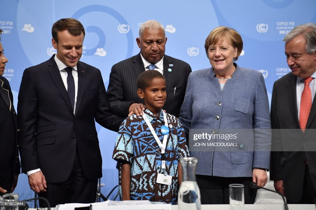 Frank Bainimarama (C-top), Prime Minister of Fiji and President of COP 23, French President Emmanuel Macron (L), German Chancellor Angela Merkel (2ndR) and UN Secretary-General Antonio Guterres (R) pose with a young Fijian boy who will give a speech before the opening session at the UN conference on climate change (COP23) on November 15, 2017 in Bonn, western Germany. / AFP PHOTO / John MACDOUGALL