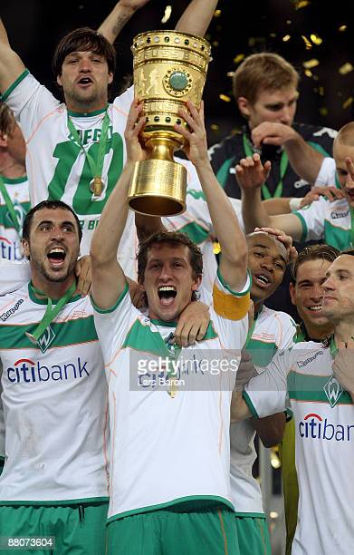 Frank Baumann of Bremen lifts the trophy after winning the DFB Cup Final match between Bayer 04 Leverkusen and SV Werder Bremen at Olympic Stadium on...