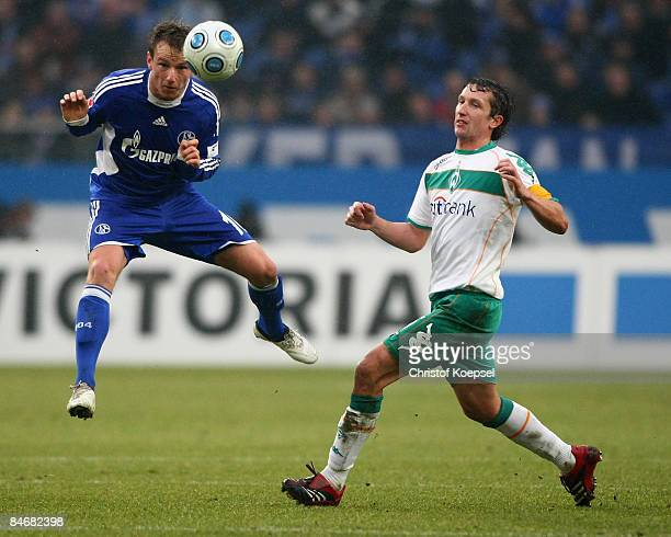 Frank Baumann of Bremen tackles Ivan Rakitic of Schalke during the Bundesliga match between FC Schalke 04 and Werder Bremen at the VeltinsArena on...