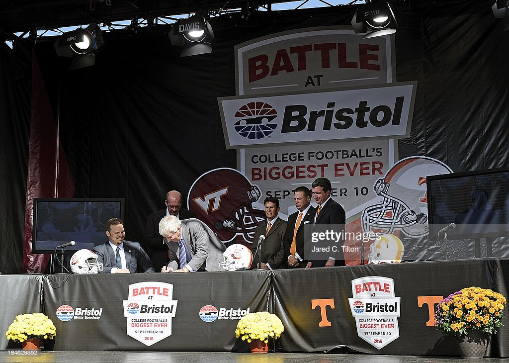 Frank Beamer, Virginia Tech Head Coach, signs a contract as (L-R) Marcus Smith, President/COO Speedway Motorsports, Jim Weaver, Virginia Tech Athletic Director, Dave Hart, Tennessee Vice Chancellor/Athletic Director, Butch Jones, Tennessee Head Coach, and Jerry Caldwell, General Manager Bristol Motor Speedway, look on at Bristol Motor Speedway on October 14, 2013 in Bristol, Tennessee. Bristol Motor Speedway plans to transform the legendary Speedway into the world's largest football stadium for the inaugural Battle at Bristol, College Football's Biggest EVER game to be held on Saturday, September 10, 2016. The event will feature a border battle between the Virginia Tech Hokies and Tennessee Volunteers and is projected to set the NCAA record for highest single-game attendance.