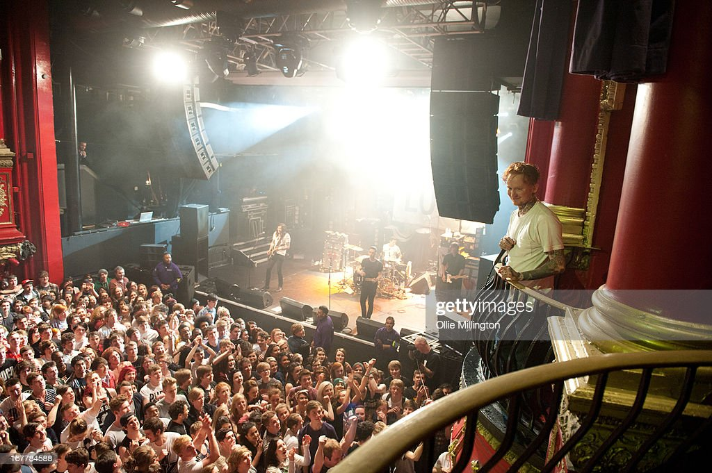 Frank Carter of Pure Love performs from the VIP balconey as the rest of Pure Love perform onstage during a sold out show at KOKO on April 18 2013 in...