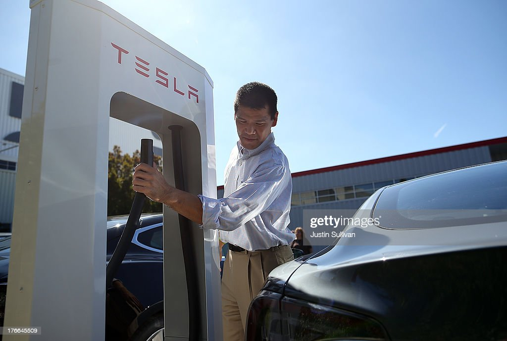 Frank Chou prepares to plug the Tesla Supercharger into his Tesla Model S sedan outside of the Tesla Factory on August 16, 2013 in Fremont, California. Tesla Motors opened a new Supercharger station with four stalls for public use at their factory in Fremont, California. The Superchargers allow owners of the Tesla Model S to charge their vehicles in 20 to 30 minutes for free. There are now 18 charging stations in the U.S. with plans to open more in the near future.