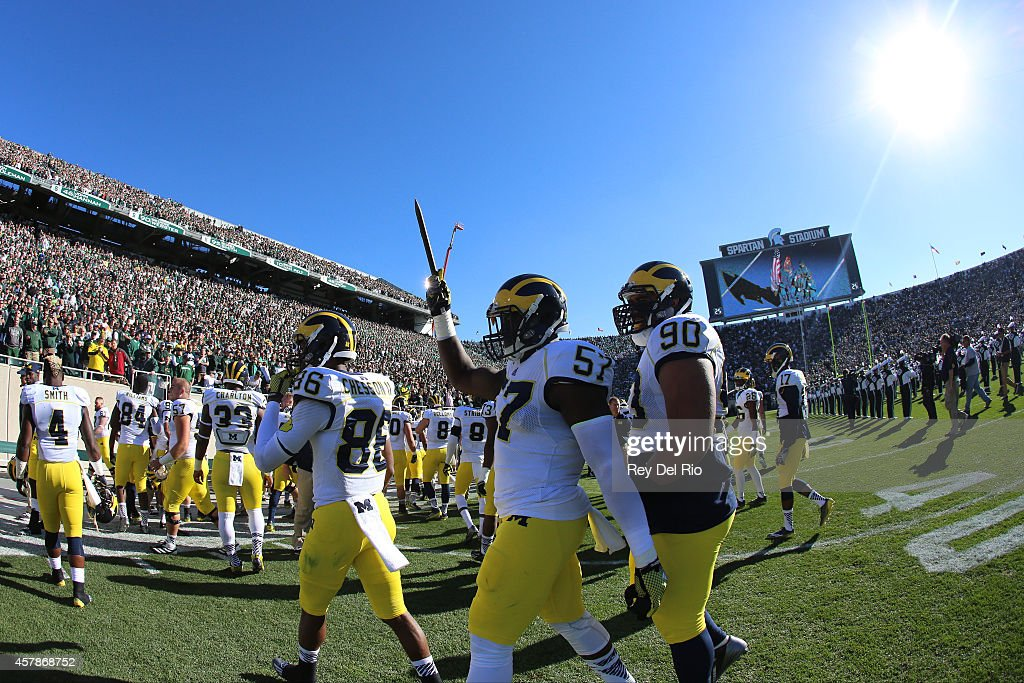 Frank Clark of the Michigan Wolverines holds up a stake prior to the start of the game against the Michigan State Spartans at Spartan Stadium on...