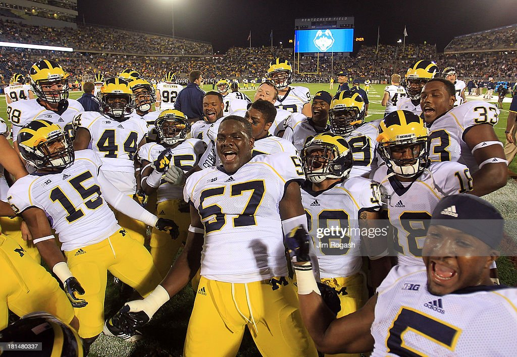 Frank Clark #57 of the Michigan Wolverines leads is team in a chant before a game with the Connecticut Huskies at Rentschler Field on September 21, 2013 in East Hartford, Connecticut.