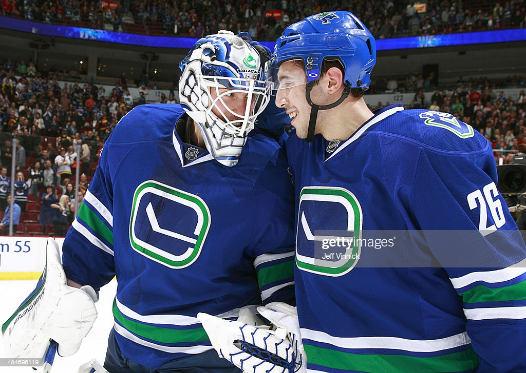Frank Corrado #26 and Jacob Markstrom #35 of the Vancouver Canucks celebrate a victory over the Calgary Flames in their NHL game at Rogers Arena April 13, 2014 in Vancouver, British Columbia, Canada. Vancouver won 5-1.