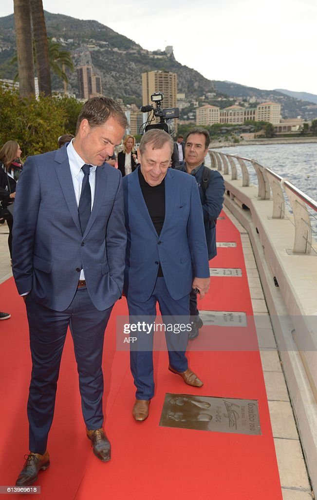 Frank de Booer (Left) Dutch football manager of Inter Milan and Golden Foot President Antonio Caliendo look at footballer Francesco Totti's foot print along the The Champions Promenade along the sea front during the 2016 Golden Foot Awards day in Monaco on October 11, 2016. / AFP / Yann COATSALIOU