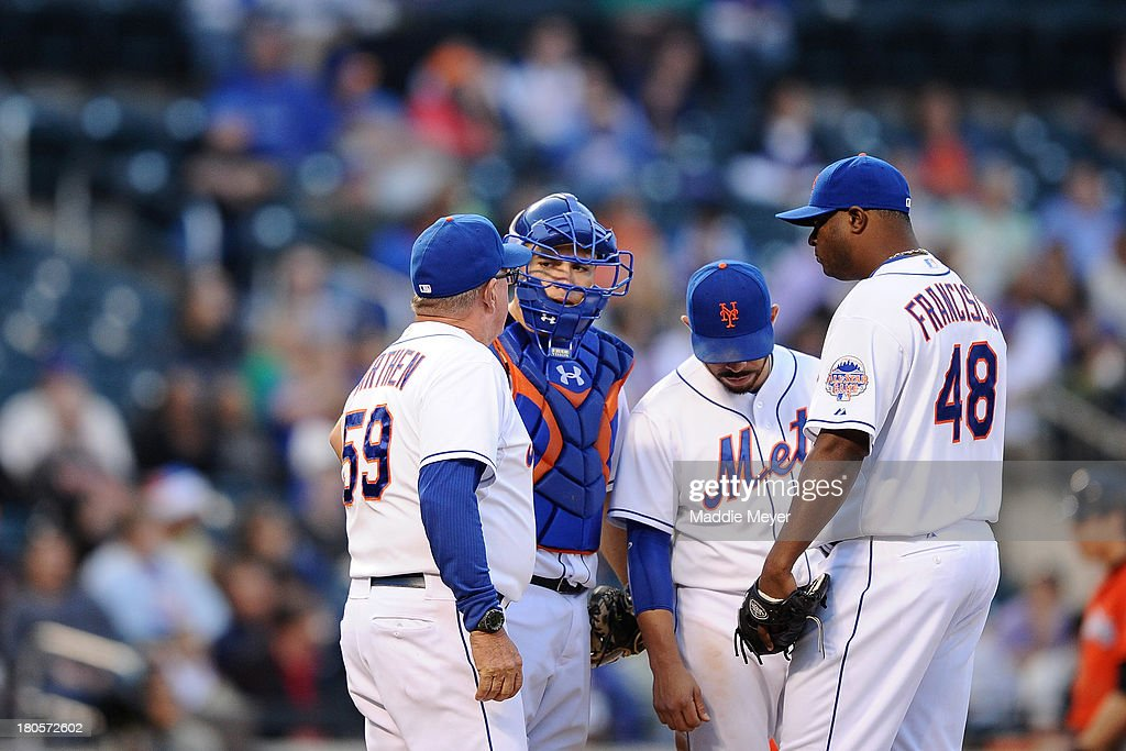 Frank Francisco #48 of the New York Mets talks with teammates Dan Warthen #59, Travis d'Arnaud #15, and Omar Quintanilla #3 after walking Justin Ruggiano #20 of the Miami Marlins during the eighth inning at Citi Field on September 14, 2013 in the Flushing neighborhood of the Queens borough of New York City.
