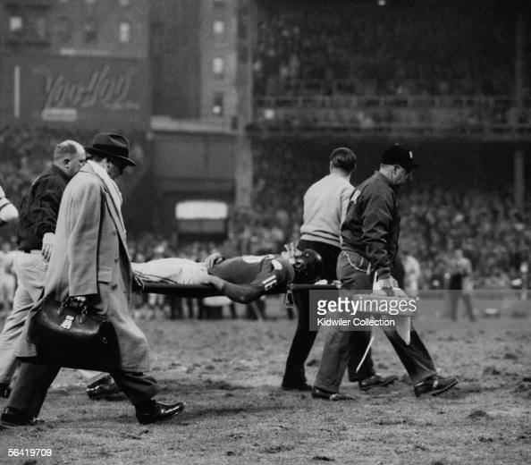 Frank Gifford of the New York Giants is taken from the field after being hit by Chuck Bednarik of the Philadelphia Eagles to stop the last chance the...