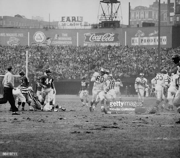 Frank Gifford of the New York Giants lays on the field after being hit by Chuck Bednarik of the Philadelphia Eagles to stop the last chance the...