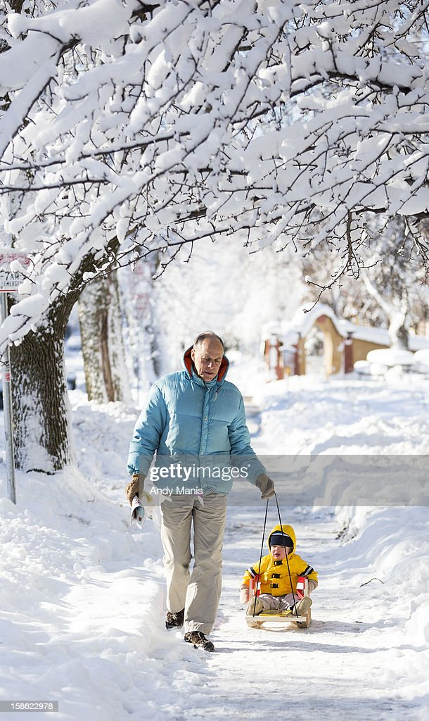 Frank Gloss pulls his grandson, Liam, 17 months old, along a sidewalk December 21, 2012 in Madison, Wisconsin, a day after Wisconsin was blanketed with a record snow storm.
