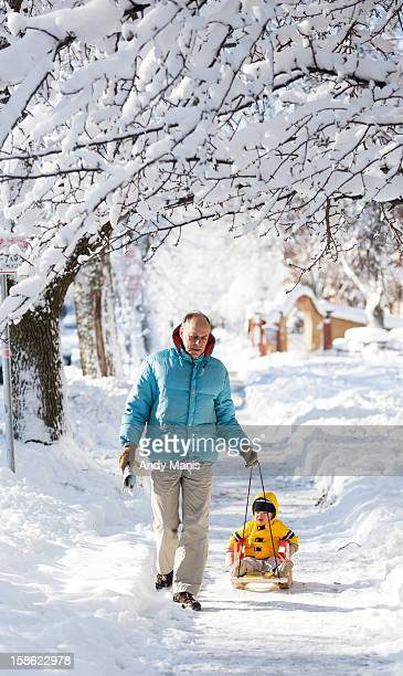 Frank Gloss pulls his grandson Liam 17 months old along a sidewalk December 21 2012 in Madison Wisconsin a day after Wisconsin was blanketed with a...