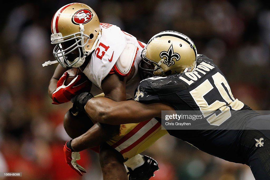 Frank Gore #21 of the San Francisco 49ers is tackled by Curtis Lofton #50 of the New Orleans Saints at The Mercedes-Benz Superdome on November 25, 2012 in New Orleans, Louisiana. The 49ers defeated the Saints 31-21.